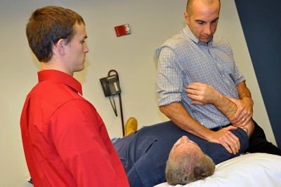 Current DPT student Gregory Sago gets hands-on instruction from UConn Health Center physical therapist Gregg Gomlinski as part of his clinical experience. (Shawn Kornegay/UConn Photo)
