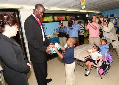Photo caption: Emeka Okafor greets children at Hartford's Clark Elementary School in 2007. UConn Foundation