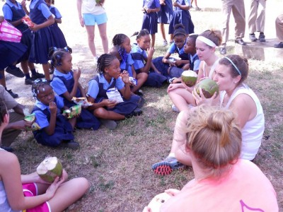 Alexandria Cipolla (top) and Shelby Flynn and another student enjoy drinking coconuts with students from Cove Elementary School in Jamaica.